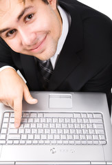 Smiling businessman pressing button on laptop keyboard.