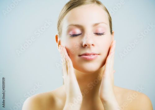 Young beautiful woman massaging face.