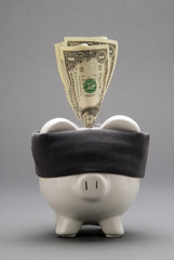 Blindfolded piggy bank sucking in American dollar bills.