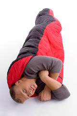 young man covered himself with red sleeping bag background