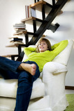 Portrait of young woman relaxing in chair at home. poster