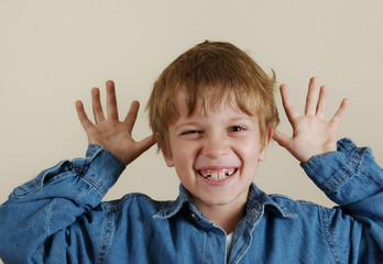 Young caucasian gesturing boy in blue shirt