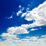 blue sky is covered by white fluffy clouds poster