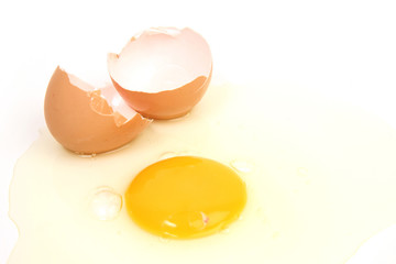 cracked egg with yolk spilt out on white background