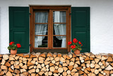 Window with flowers and chopped firewood in Mittenwald poster