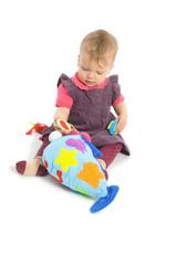 baby girl sitting on floor playing with stuffed animal toy.