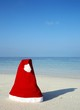 Christmas hat on a white sandy beach in the Indian Ocean
