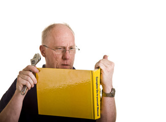 An older man looking at a repair book holding a wrench