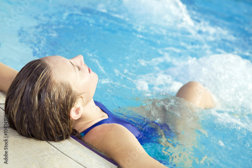 Portrait of young woman sitting in swimming pool