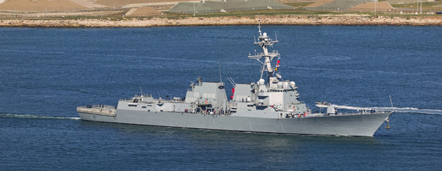 Arleigh Burke-class guided missile destroyer leaving port.
