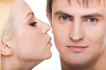 Handsome guy looking at camera with girl kissing him