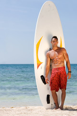 male at the beach standing next to his surfboard