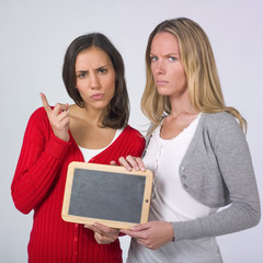 Two women accusing with a blank blackboard