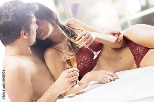 Couple kissing and drinking on the bed in bedroom