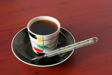 cup of the hot drink and medical thermometer