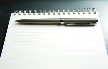 The notebook with the handle lays on a grey background