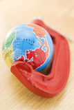 Political Globe Squeezed In Clamp On Wooden Surface poster