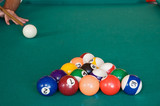 Playing billiards with balls on a green felt table poster