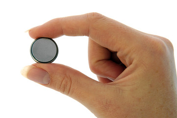Isolated image of a small watch battery held between fingers