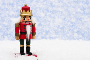 Nutcracker sitting on snow with snowflake background