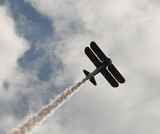 Vintage biplane performing an aerial stunt with smoke poster