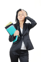 Businesswoman with documents and pen suffering from headache