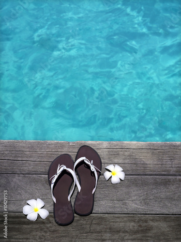 women sandals on a wooden floor with flowers near the water