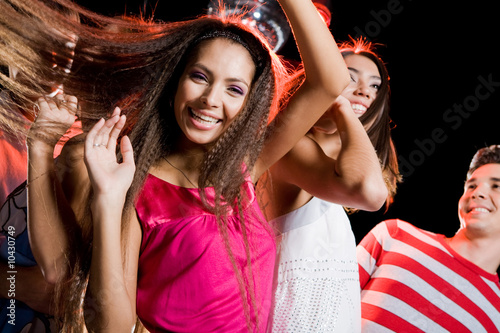 Portrait of cheerful girl dancing at party with her friends