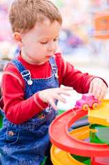 4-year old caucasian boy playing with a toy car (shallow DOF)