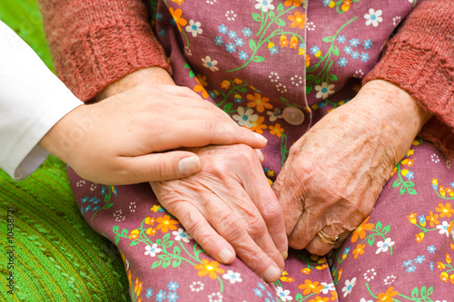A doctor holding an old woman's hand - part of a series.