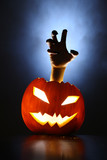 Hand of horror raising from glowing pupmkin lantern.