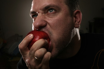 Tough man eating red apple. Close-up.