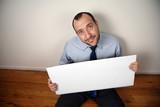 Businessman begging for help with cardboard sign poster