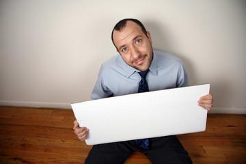 Businessman begging for help with cardboard sign