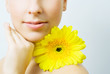 Young woman with yellow gerbera flower.