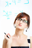 The girl in glasses thoughtfully looks at formulas poster