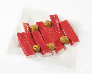 Surimi sticks in a plate with olives on a white background