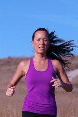 beautiful female jogger i purple top running in late afternoon