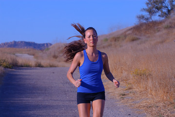 beautiful jogger in blue top running in late afternoon