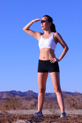 Female jogger with beautiful toned body shielding her eyes