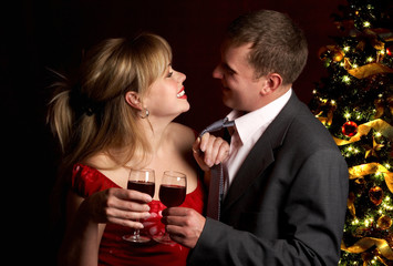 Happy couple in love and Christmas tree. Over dark  background.