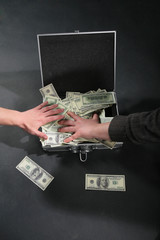 Two hands and suitcase with dollars