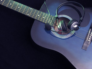 acoustic guitar and headphones on black background