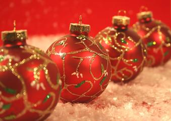 Four chritmas ball on snow carpet. (close-up)