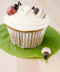cupcake decorated with a bee and a ladybug on leaf