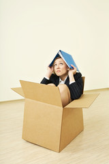 The woman in a business suit sitting in a cardboard box