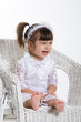 Little Girl Sitting in a rotton armchair crying