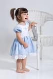 Little girl standing near the rotton armchair crying poster