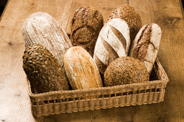 Basketful of different types of bread on a wooden table