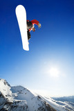 Snowboarder jumps in air with blue sky background